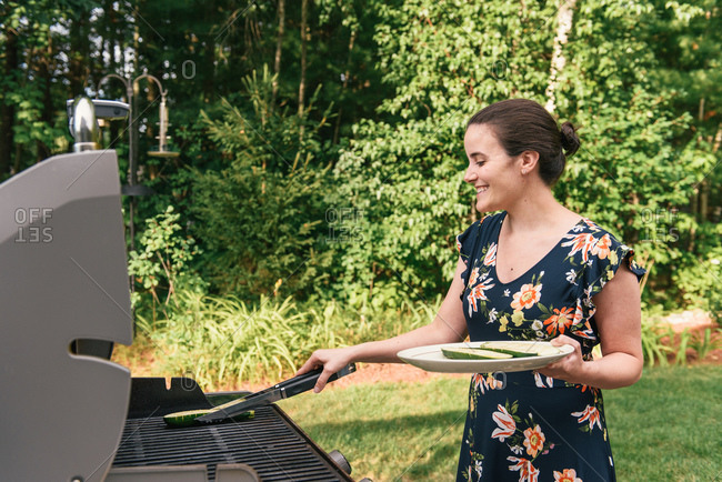 Vegetarian woman placing squash zucchini on the grill in backyard