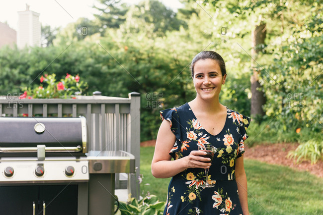 Half body crop of smiling woman holding wine in landscaped back yard