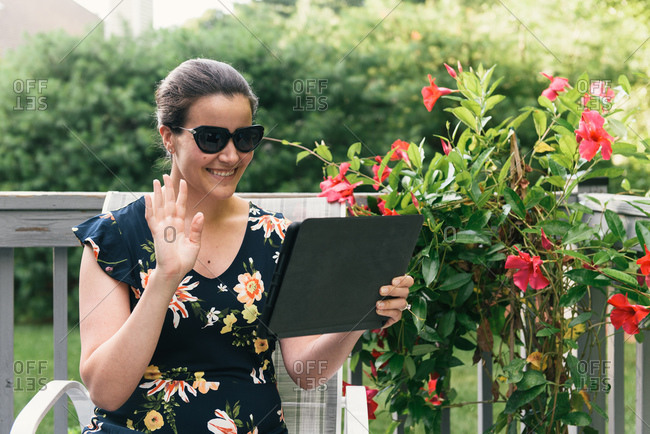 Smiling stylish woman on video call from tablet in floral back yard