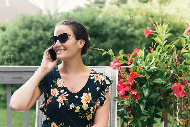 Half body crop of woman on cell phone and smiling with flowers outside