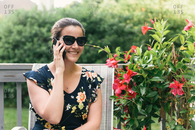 Adult woman smiling on phone call from back patio with flower plant