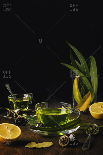 Cup of green tea on a wooden table with eucalyptus, spices and lemons