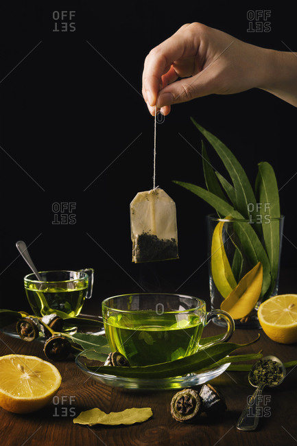 Person puts a bag of herbs in a cup of tea with eucalyptus and lemons