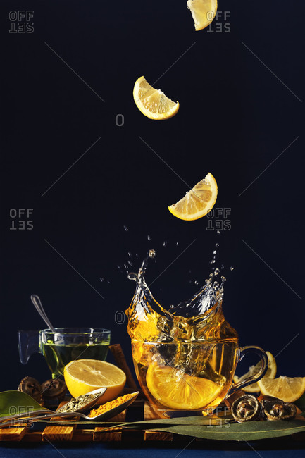 Lemon slices fall into a cup of tea with spices and eucalyptus leaves