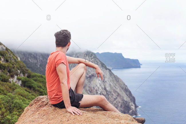 A man on a rock, looking at cliffs and ocean, mountains and fog