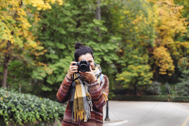 A woman in a sweater and scarf taking pictures in an autumn forest