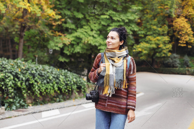A young woman in a sweater in an autumn forest with a camera