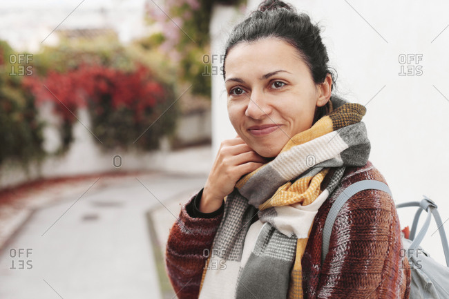Woman in warm scarf and backpack smiling, in an old town