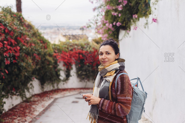 Woman with a backpack looking at the camera, old town of spain