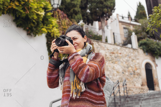 A woman tourist with a camera on the streets of grande, portugal