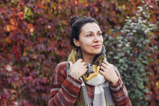 Pretty woman in scarf and sweater, autumn park, red leaves