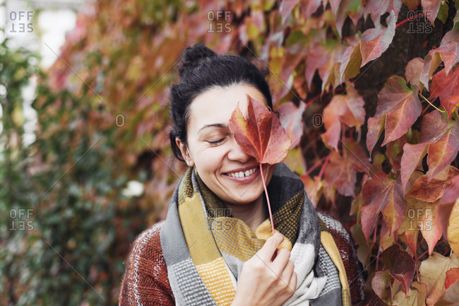 A young woman covers her face with a red leaf and laughing tr
