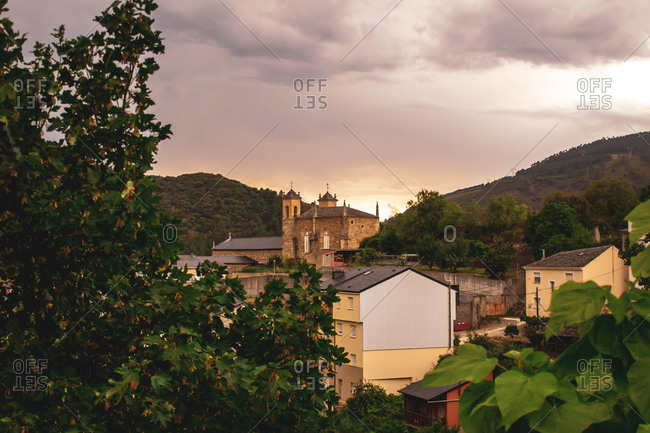 Castle in the middle of village with mountains in cloudy sunset