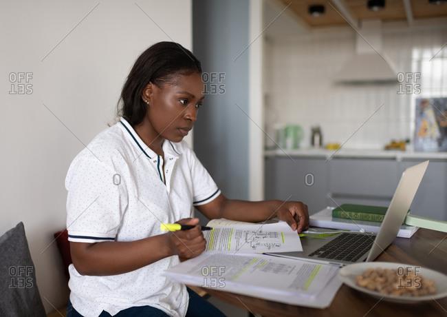 Ethnic student doing homework on bed
