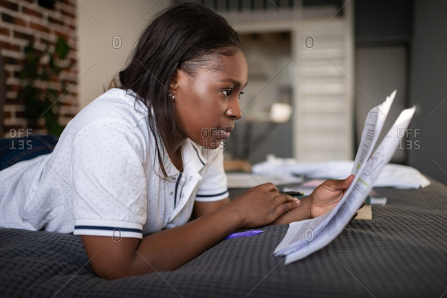 Black woman reading papers on bed