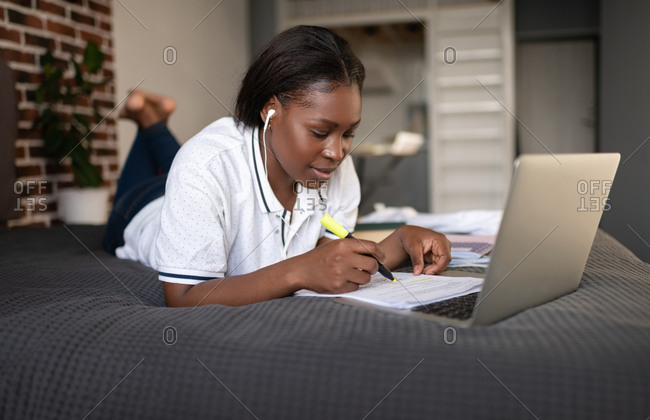 Black student making notes during online lesson