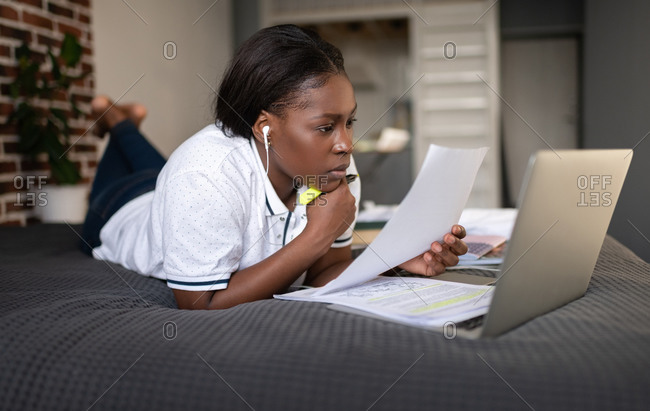 Thoughtful black woman reading paper during online lesson
