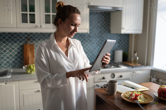 Businesswoman browsing tablet during breakfast