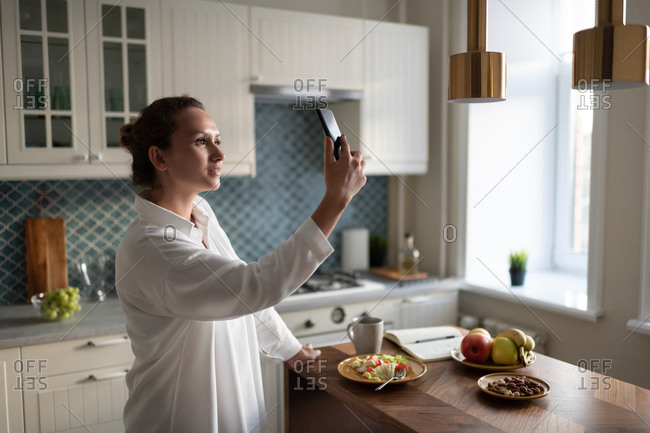 Businesswoman using smartphone for communication in kitchen