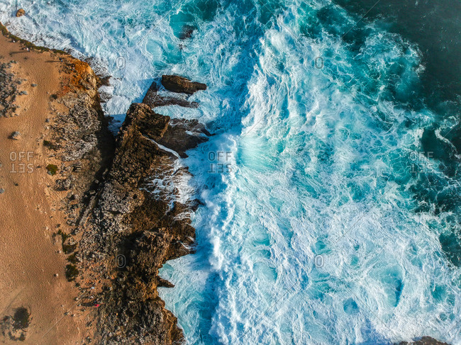 Aerial top view of sea waves hitting rocks on the beach with turquoise