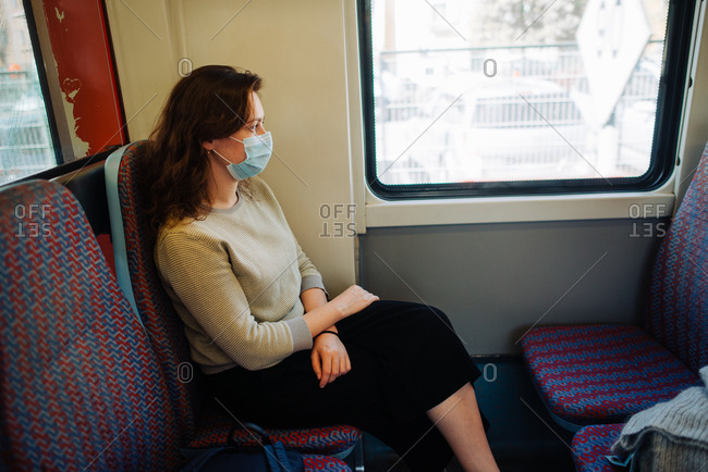 Young woman wearing medical mask while sitting in transport