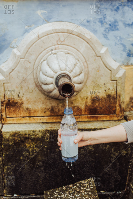Woman filling plastic bottle with spring water