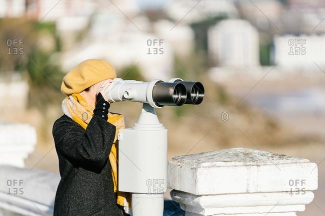 Woman on vacation looking through binoculars