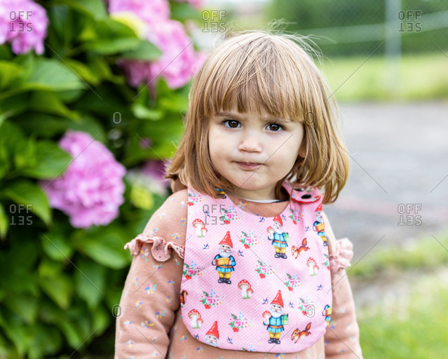 Girl with serious gesture and pink bib looks at the camera