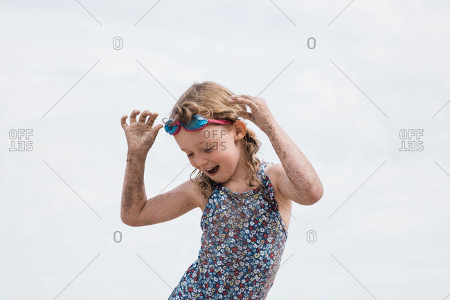 Girl with goggles on dancing having fun at the beach in summer