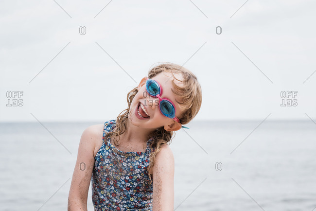 Young girl laughing with her goggles on whilst playing at the beach