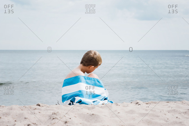 Young boy sat wrapped in a striped towel alone on the beach