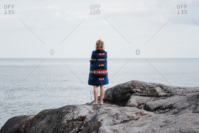 Woman standing on rocks wrapped in a pendleton blanket in sweden