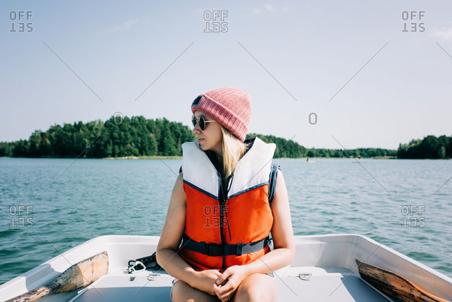 Woman sitting peacefully on a rowing boat in summer on a lake
