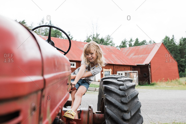 Girl sat on a tractor smiling whilst at a farm in sweden