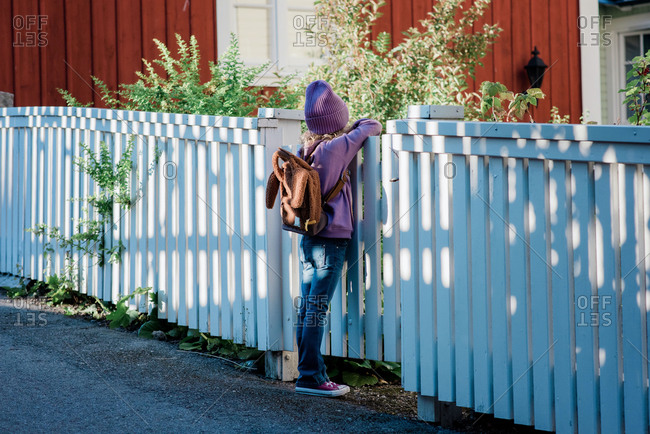 Young girl leaning on a fence looking into the distance waiting