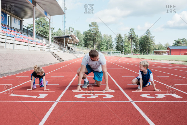 father and his kids getting ready to run on a track to race