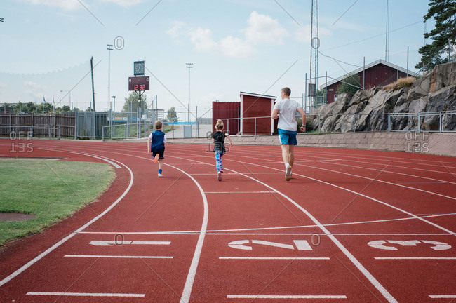 Father running with his kids on a race track