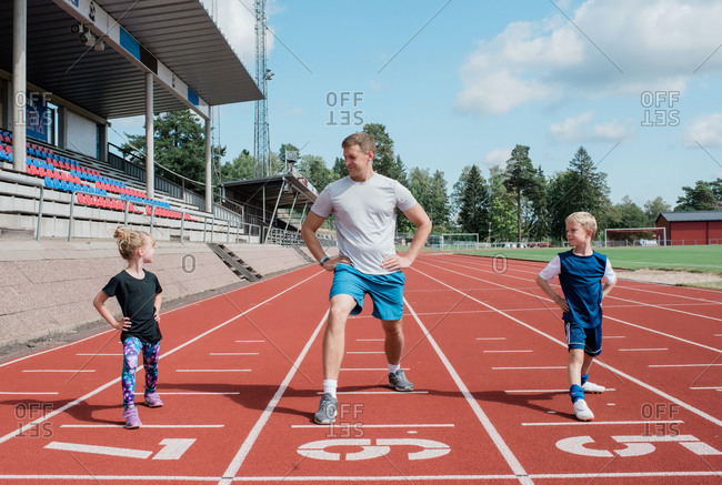 Father doing stretches with his kids on a race track