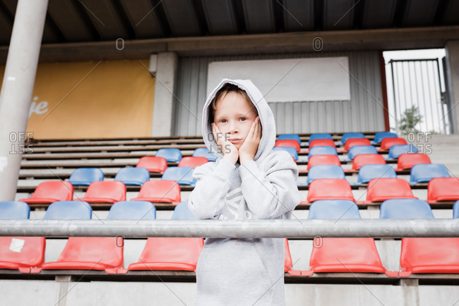 Boy looking out at a track looking nervous in sports clothes