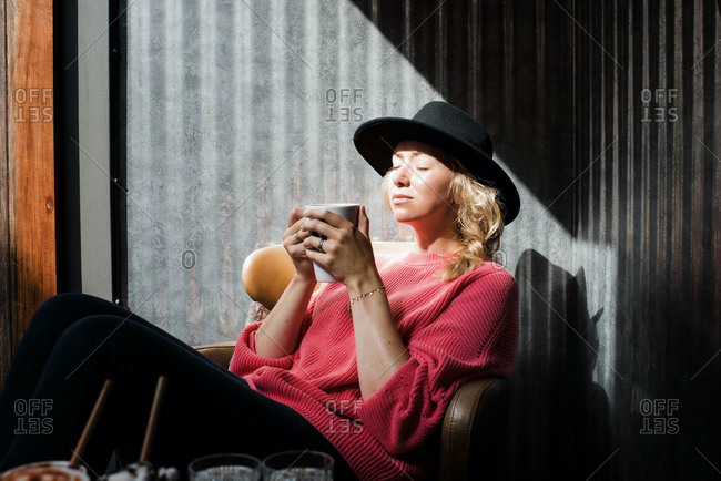 Woman sitting in a cafe holding a warm drink enjoying the sunshine