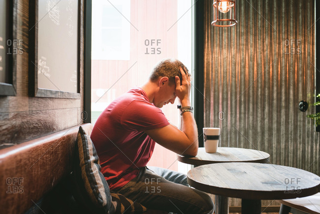 Man sat feeling stressed with his face in his hands in a cafe