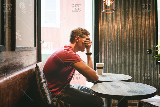 Man sat covering his face feeling stressed whilst sat in a cafe