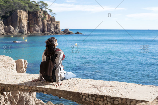 Rear view of a woman relaxing in front of blue sea, sitting on bridge