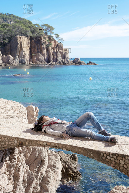 Rear view of a woman relaxing in front of blue sea, lying on bridge