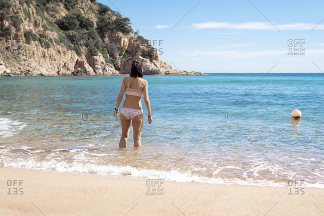 Slim girl in white panties standing against sea, rear view