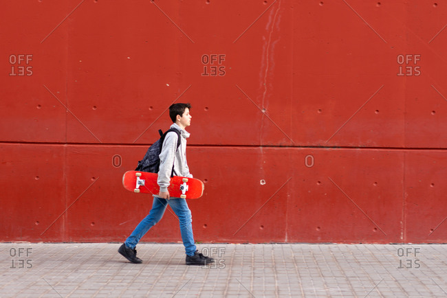 Young boy holding a red skateboard while walking against red wall