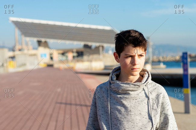 Close-up of teenage boy looking away on city promenade