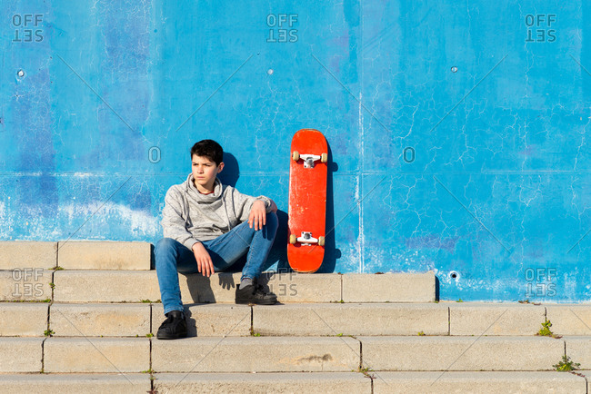 Serious teen sitting on skatepark ramp with a skateboard, looking away