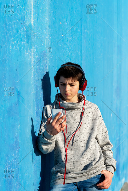 Teenager with headphones listening music while sitting on staircase.