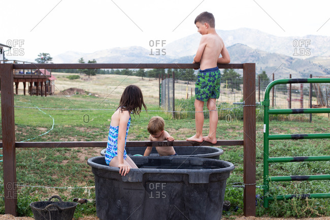 Kids playing in horse trough in the summer